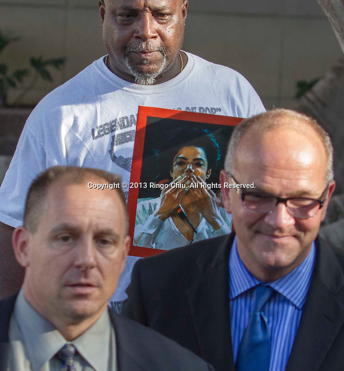 Vincent Woods, a Michael Jackson fan shows a portrait of Jackson as AEG Live lead attorney Marvin Putnam, right and Shawn Trell, left, general counsel for AEG Live, talk to reporters outside a courthouse on Wednesday, Oct. 2, 2013, in Los Angeles. A jury cleared AEG Live of negligence in a case that attempted to link the death of Michael Jackson to the company that promoted his ill-fated comeback shows. (Photo by Ringo Chiu/PHOTOFORMULA.com)