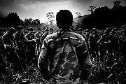 A contra commander addresses his troops as they gather in a jungle clearing.