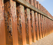 Rusty steel piling sea wall defences and shingle beach near Bawdsey Quay, Suffolk, England