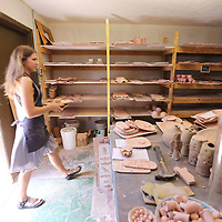 Savannah Webb brings in fired pottery that is now ready for glazing.