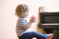 Blonde girl sits with paino clapping her hands