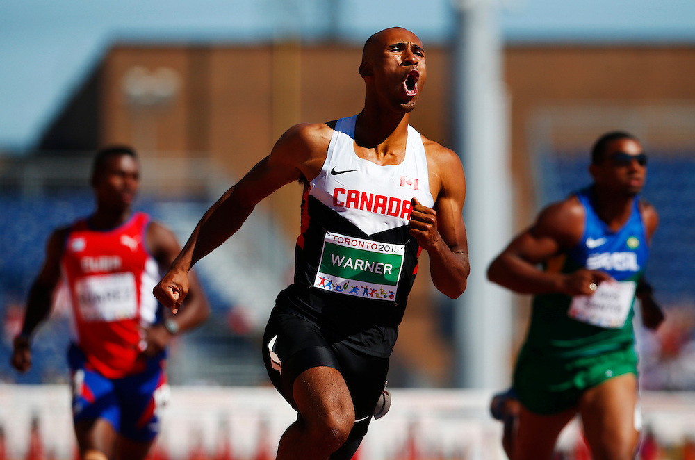 Damian Warner of Canada celebrates at at the finish line of the 110m hurdles in the men's decathlon during the athletics at the Pan Am Games in Toronto, Thursday July 23, 2015.    THE CANADIAN PRESS/Mark Blinch