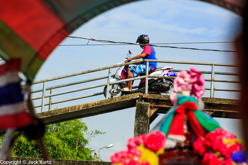 """17 NOVEMBER 2012 - BANGKOK, THAILAND:  A motorcyclist crosses bridge over a khlong or canal in the Thonburi section of Bangkok. Bangkok used to be known as the """"Venice of the East"""" because of the number of waterways the criss crossed the city. Now most of the waterways have been filled in but boats and ships still play an important role in daily life in Bangkok. Thousands of people commute to work daily on the Chao Phraya Express Boats and fast boats that ply Khlong Saen Saeb or use boats to get around on the canals on the Thonburi side of the river. Boats are used to haul commodities through the city to deep water ports for export.    PHOTO BY JACK KURTZ"""