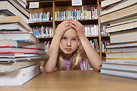 School girl sitting at desk with books in library, portrait