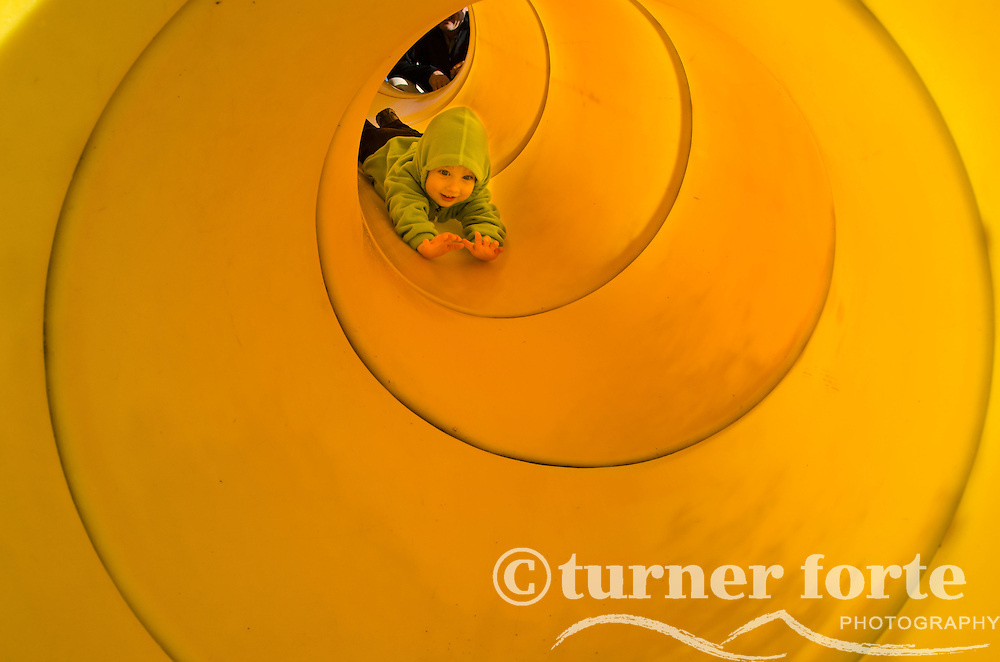 Toddler boy sliding headfirst down a yellow tubular slide in Vancouver, Canada.