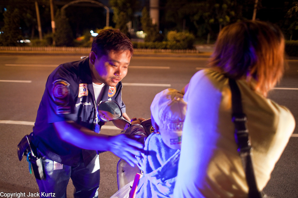 "Oct. 1, 2009 -- BANGKOK, THAILAND:  YOTHAPONG TAWATCHAI, a volunteer with Poh Teck Tung, talks a boy and his mother after they were hurt in a motorcycle accident. The 1,000 plus volunteers of the Poh Teck Tung Foundation are really Bangkok's first responders. Famous because they pick up the dead bodies after murders, traffic accidents, suicides and other unplanned, often violent deaths, they really do much more. Their medics respond to medical emergencies, from minor bumps and scrapes to major trauma. Their technicians respond to building collapses and traffic accidents with heavy equipment and the ""Jaws of Life"" and their divers respond to accidents in the rivers and khlongs of Bangkok. The organization was founded by Chinese immigrants in Bangkok in 1909. Their efforts include a hospital, college tuition for the poor and tsunami relief.    Photo by Jack Kurtz / ZUMA Press"