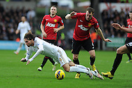 Swansea city's Michu is tackled by Utd's Phil Jones. Barclays premier league, Swansea city v Manchester Utd at the Liberty stadium in Swansea, South Wales on Sunday 23rd Dec 2012. pic by Andrew Orchard, Andrew Orchard sports photography,
