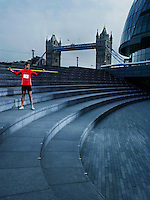 Man holding javelin on shoulders standing on steps of The Scoop amphitheatre London England
