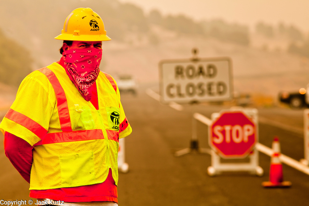 """03 JUNE 2011 - SPRINGERVILLE, AZ: Mike Taylor (CQ) from ADoT, staffs a roadblock on Highway 180 at Nelson Reservoir. The road into Nutrioso and Alpine is closed from here to south of Hannigan's Meadow.  High winds and temperatures have continued to complicate firefighters' efforts to get the Wallow fire under control. The  mandatory evacuation order for Alpine was extended to Nutrioso, about 10 miles north of Alpine and early Friday morning fire was reported on the south side of Nutrioso. The fire grew to more than 106,000 acres early Friday with zero containment. A """"Type I"""" incident command team has been called in to manage the fire.   PHOTO BY JACK KURTZ"""