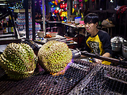 05 MARCH 2019 - BANGKOK, THAILAND:  A worker in the Ratchada Night Market grills durian, a pungent fruit popular in Southeast Asia. The Ratchada Night Market is the newest night market in Bangkok. It was originally a small night market popular with local people but now is tourism destination. Most nights the market is jammed with foreign tourists.     PHOTO BY JACK KURTZ