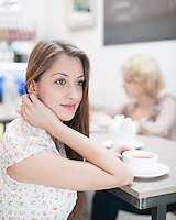 Thoughtful young woman having coffee in cafe
