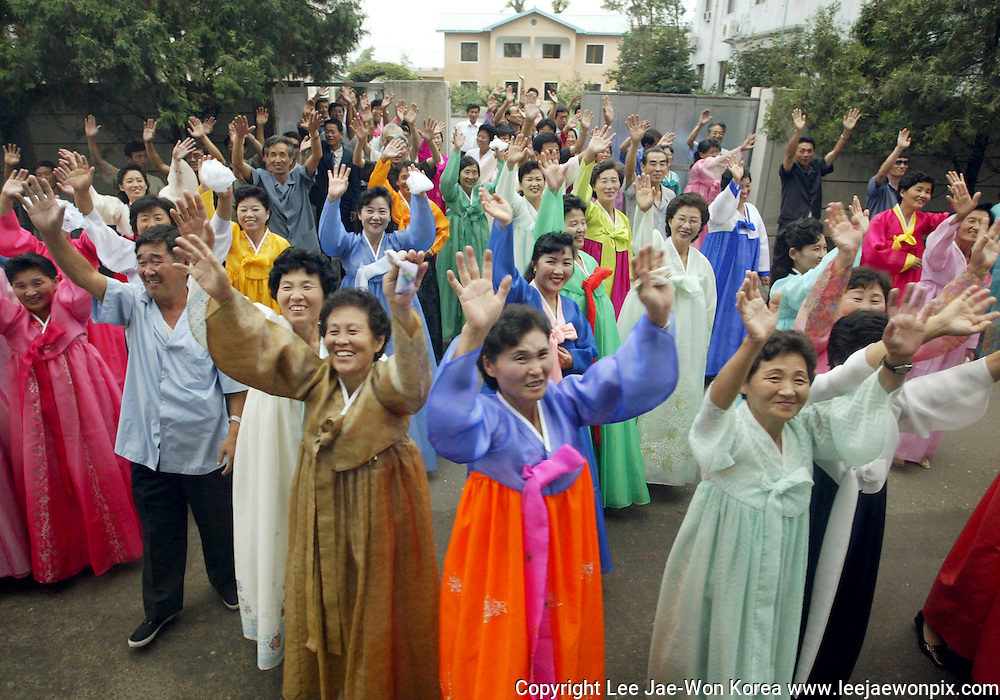 North Koreans wave to South Koreans after they read joint mass with South Koreans at a Catholic church in Pyongyang August 17, 2003. /Lee Jae-Won
