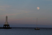 A nearly full moon rises above Lake Michigan over the Port Washington, Wi., lighhouse as fisherman and sailors enjoy the view.