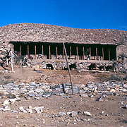 2-4 December 1976<br /> Verandah roof resting on poles. Stone foundation with arched recesses. Stone wall without mortar in foreground.