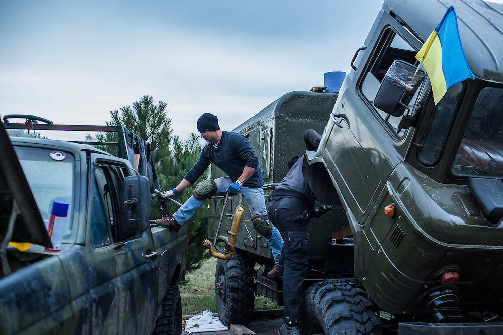 Men repair trucks at the base of the Azov Battalion, a pro-Ukraine militia, on Wednesday, October 15, 2014 in Urzuf, Ukraine. Photo by Brendan Hoffman, Freelance