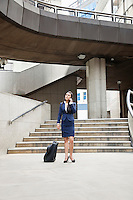 Young Indian businesswoman using cell phone with luggage outdoors