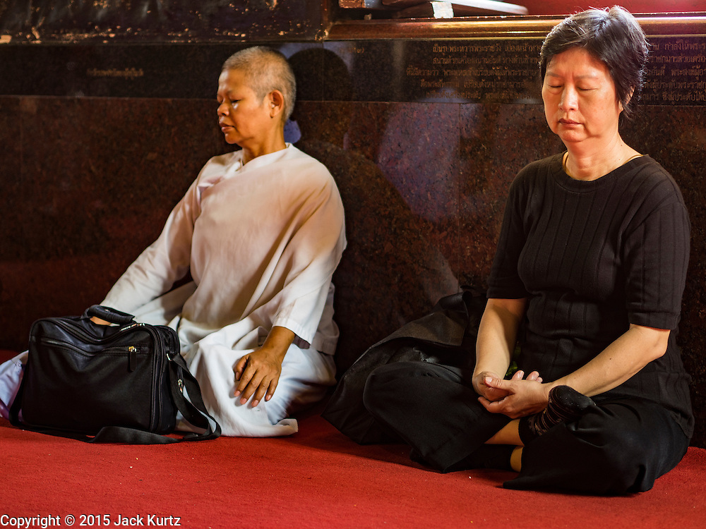 14 DECEMBER 2015 - BANGKOK, THAILAND:   Women pray and meditate for the Supreme Patriarch before the start of his funeral at Wat Bowon Niwet in Bangkok. Somdet Phra Nyanasamvara, who headed Thailand's order of Buddhist monks for more than two decades and was known as the Supreme Patriarch, died Oct. 24, 2013, at a hospital in Bangkok. He was 100. He was ordained as a Buddhist monk in 1933 and appointed as the Supreme Patriarch in 1989. He was the spiritual advisor to Bhumibol Adulyadej, the King of Thailand when the King served as a monk in 1956. His funeral, which will take three days,   Dec. 15-17, will be attended by thousands of Thais and most of the Royal Family. Buddhist clergy from around the world are expected to attend.     PHOTO BY JACK KURTZ
