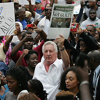 "A George Zimmerman supporter (white shirt) stirs up the crowd as protesters march and hold signs in the No Justice No Peace- ""March Against Gun Violence""  walk from Lake Eola in downtown Orlando, to the Orange County Courthouse on Wednesday, July 17, 2013. The march was organized by the Modarres Law Firm and Orlando attorney Natalie Jackson, one of the attorneys for Trayvon Martins parents. (AP Photo/Alex Menendez)"