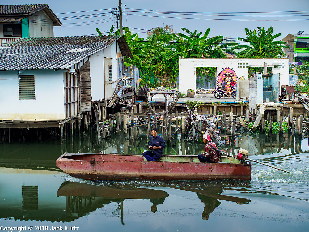 "22 MARCH 2018 - BANGKOK, THAILAND: A boat goes past a demolished home on the bank of Khlong Lat Phrao. Bangkok officials are evicting about 1,000 families who have set up homes along Khlong  Lat Phrao in Bangkok, the city says they are ""encroaching"" on the khlong. Although some of the families have been living along the khlong (Thai for ""canal"") for generations, they don't have title to the property, and the city considers them squatters. The city says the residents are being evicted so the city can build new embankments to control flooding. Most of the residents have agreed to leave, but negotiations over compensation are continuing for residents who can't afford to move.      PHOTO BY JACK KURTZ"