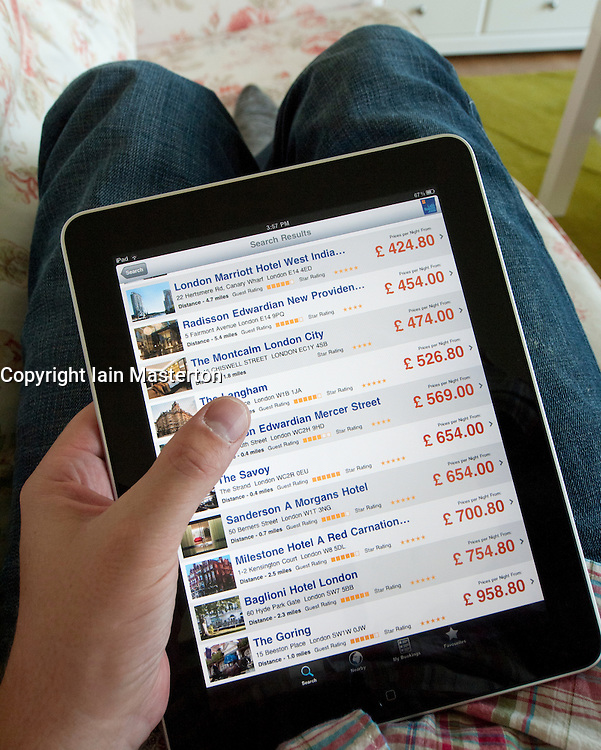 Man booking hotel in London using app for comparing hotel prices on an iPad touch screen tablet computer