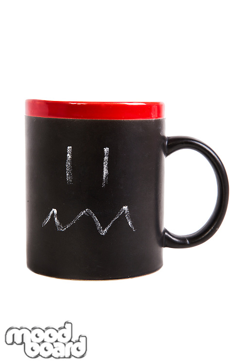 Close-up of angry expression drawn on cup over white background
