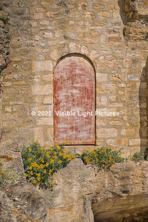 A faded doorway with flowers at Chateau de Baux