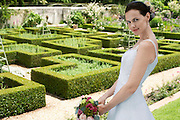 Mid adult bride in garden holding bouquet side view