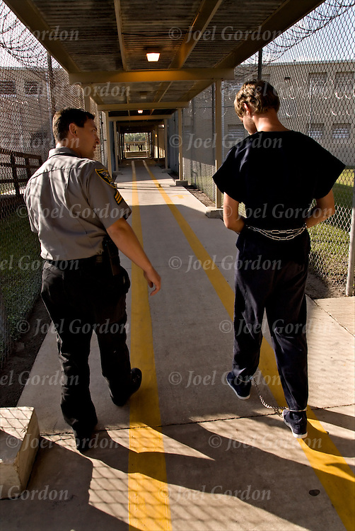 Correction Officer taking handcuffed and shackled inmate back to jail cell block walking the yellow lines.