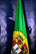 The shadow of the presidential candidate Cavaco Silva near Portugal national flag.