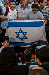 A Jewish young man presents an Israeli national flag to the three Israeli teens at a joint funeral at a cemetery in Modi'in near Jerusalem, on July 1, 2014. The three Israeli teens whose bodies were found Monday evening were brought to rest side by side on Tuesday at a joint funeral held in Modi'in near Jerusalem. Tens of thousands of people participated in the funeral, including Prime Minister Benjamin Netanyahu and President Shimon Peres, who eulogized the three, whose caskets were wrapped with Israeli flags. EXPA Pictures © 2014, PhotoCredit: EXPA/ Photoshot/ Li Rui<br /> <br /> *****ATTENTION - for AUT, SLO, CRO, SRB, BIH, MAZ only*****