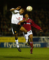 Photo: Scott Heavey.<br /> Northampton Town v Manchester United. FA Cup Fourth Round. 25/01/2004.<br /> Quentin Fortune out-jumps Derek Asamoah
