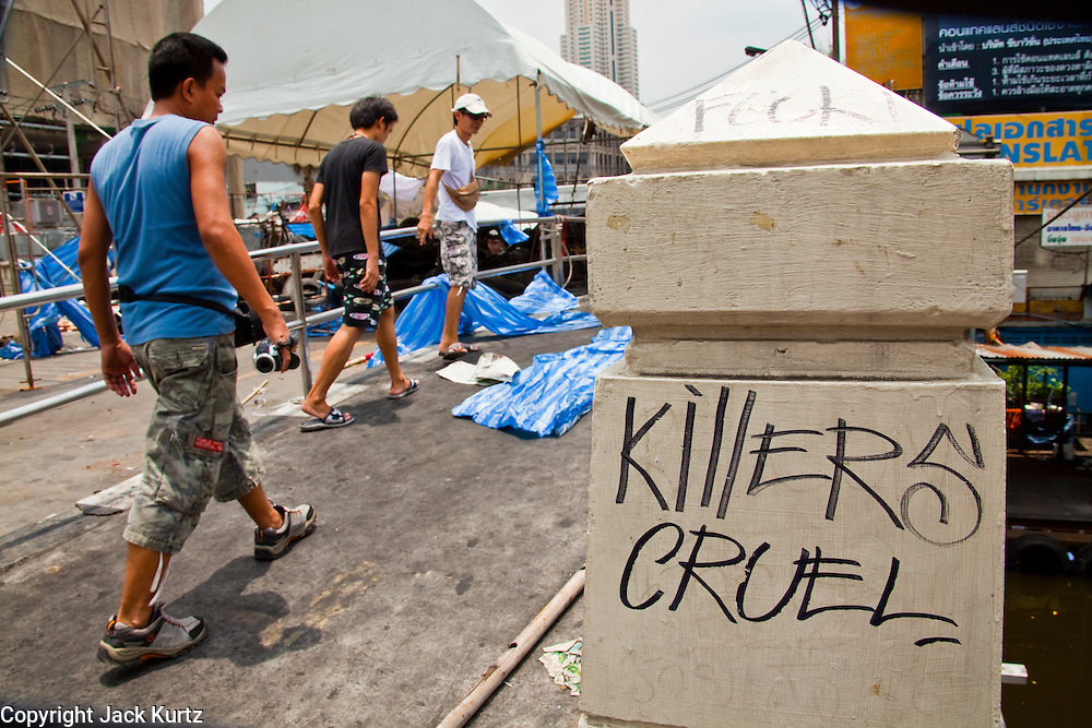 20 MAY 2010 - BANGKOK, THAILAND: Pedestrians pass anti government graffiti as they cross a canal bridge near the Ratchaprasong Intersection in Bangkok Thursday. The day after a military crackdown killed at least six people, Thai authorities continued mopping up operations around the site of the Red Shirt rally stage and battle fires set by Red Shirt supporters in the luxury malls around the intersection. PHOTO BY JACK KURTZ
