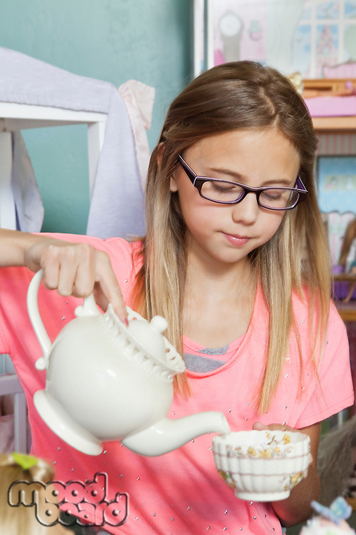 Little girl playing with tea set