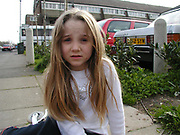 Kid sitting on the pavement staring into the camera, UK, 2000's