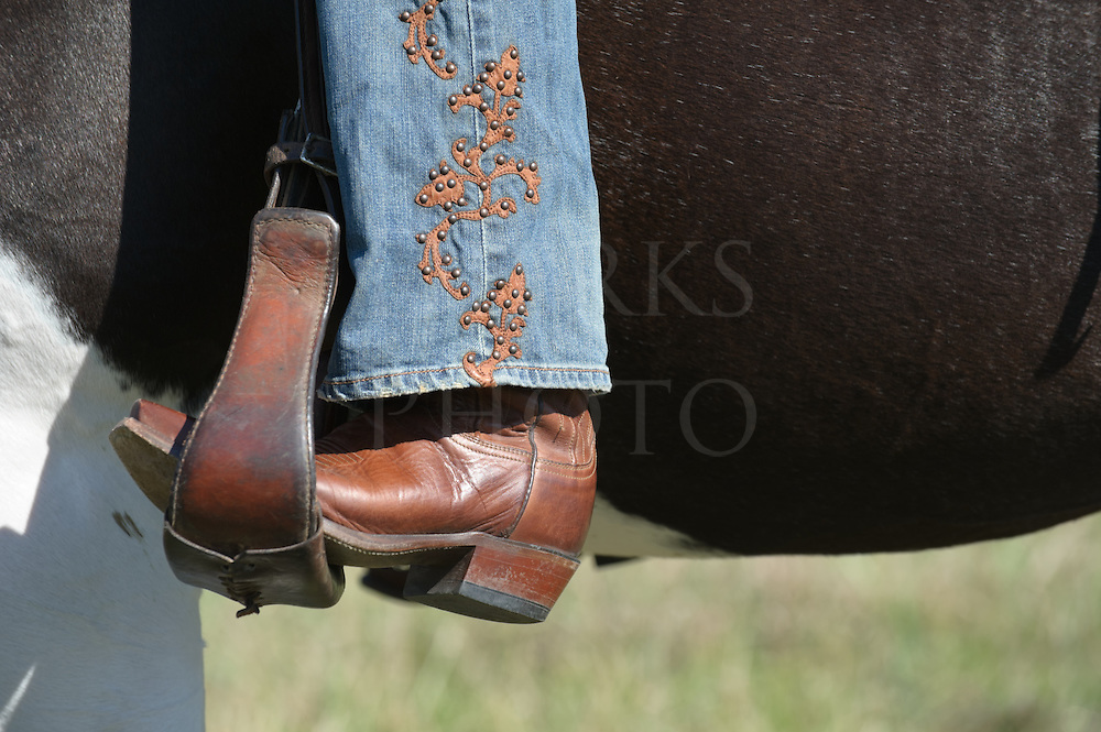 Boot in stirrup and fancy blue jeans and boot of a woman horseback riding western style, close up in sunlight with copy space.
