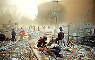 Injured firefighters are treated after collapse of the World Trade Center...This photograph was awarded the 2002 Pulitzer Prize for Breaking News Photography.
