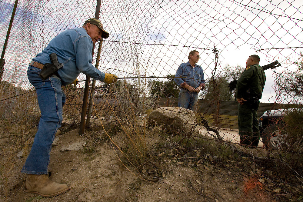 Bob Maupin, a border rancher along the U.S. Mexico border in Campo, California, repairs fence cut by smugglers moving undocumented immigrants into the country through his property on January 20, 2009. On other side is Dick Buck, left, a Minuteman Civil Defense Corps volunteer, and a US Customs and Border Protection agent. Please contact Todd Bigelow directly with your licensing requests.