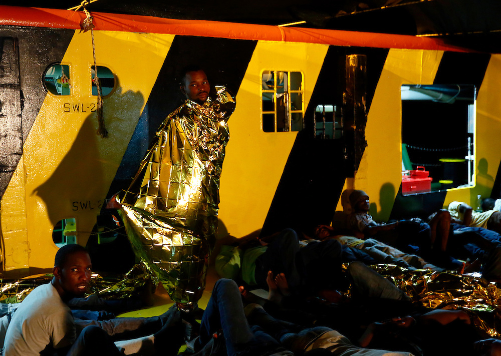 A migrant wraps himself in an emergency space blanket to prepare for a night's sleep on the deck of the Medecins san Frontiere (MSF) ship Bourbon Argos off the coast of Libya August 7, 2015.  Some 241 mostly West African migrants on the ship are expected to arrive on the Italian island of Sicily on Sunday, according to MSF.<br /> REUTERS/Darrin Zammit Lupi <br /> MALTA OUT. NO COMMERCIAL OR EDITORIAL SALES IN MALTA