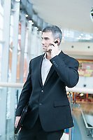 Businessman walking and talking on mobile phone