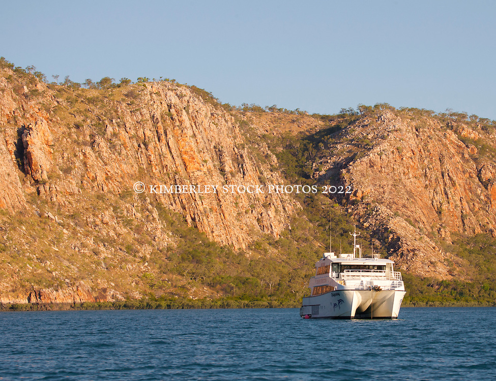 Charter boat MV Odyssey against the stunning sandstone cliffs of Dugong Bay on the Kimberley coast.