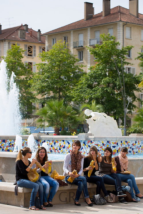 Young office workers eat sandwiches in Place Clemenceau during lunch break in Pau, the Pyrenees, France