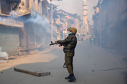 December 18, 2018 - Srinagar, Jammu & Kashmir, India - Indian policeman seen firing tear smoke canister towards Protestors during clashes in Srinagar. Clashes erupted soon after the Protestors were detained by Indian policemen in Srinagar during a protest march against the recent civilians killings. The march Protest were called by Separatist leaders after the Indian army killed seven civilians in Pulwama district of Jammu and Kashmir recently. (Credit Image: © Idrees Abbas/SOPA Images via ZUMA Wire)