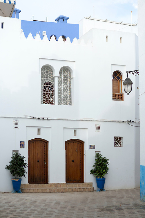 Moroccan door architecture, Asilah, Northern Morocco, 2015-08-11.<br /><br />Asilah is a sleepy fishing town in the North of Morocco, just one hour south of Tangier. While not completely off Morocco's well-beaten path, it's often missed by travellers bound inland for Fez or Chefchaouen, yet has a uniquely alluring charm. With an immaculately restored medina that's re-painted vivid shades of blue & white each summer, Asilah has the feel of being Morocco's own Santorini - a great spot to see the more chilled out, seaside town life in Morocco.  <br /><br />The architecture in Asilah has been heavily influenced by these different periods of occupation, which is one of the main reasons for its unique and characterful feel. Evidence of Mediterranean design can be seen in the rampart walls and gates themselves, reflecting the Spanish & Portuguese influence on the Asilah's development, Roman ruins can be found in the nearby town of Larache and Arab influences are more subtly found in the decorative window shutters and the labyrinth like medina layout to the streets. <br /><br />If a lover of the quirkier details found in the medinas of Morocco, then Asilah won't disappoint, with hundreds of creatively designed doorways, decorative window shutters and retro, old electricity & water metres from the French occupational period. Together with the art work and murals spread throughout the medina, these little details all paint the picture of Asilah. One of the main things to do is to simply wander the streets and take in all the unusual textures, shades & charm the town has to offer.