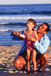 little girl and man flying a kite together at the beach in East Hampton, NY