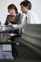 Two business colleagues using laptop at conference table