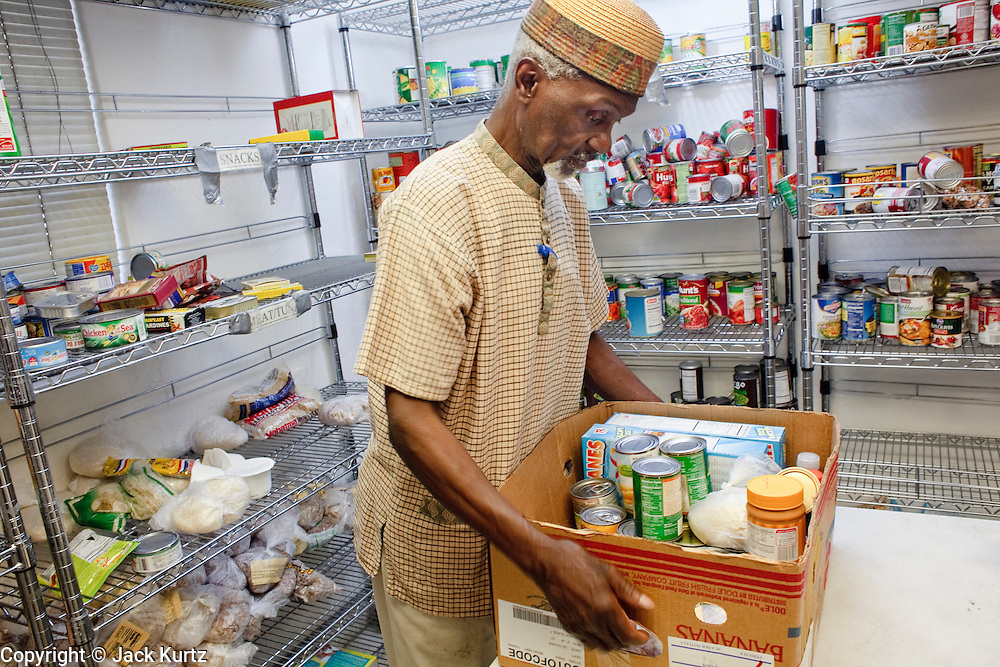 22 JUNE 2009 - PHOENIX, AZ: Habibulllah Saleem, husband of Cultural Cup food bank founder Zarinah Awad, prepares boxes of food before distributing them at the food bank. The Cultural Cup has become a sort of community center. It started as a food bank and has since grown to include a clothing bank and free walk in clinic. The walk in clinic at the Cultural Cup Food Bank started two years ago when Cultural Cup founder Zarinah Awad wanted to expand the food bank's outreach and provide basic medical care for the people who use the food bank. The clinic sees, on average, 7 - 11 patients a week. Awad said that as the economy has worsened since the clinic opened and demand has steadily increased. She attributes the growth to people losing their jobs and health insurance. The clinic is staffed by volunteers both in the office and medical staff. Adults are seen every Saturday. Children are seen one Saturday a month, when a pediatrician comes in. Awad, a Moslem, said the food bank and clinic are rooted in the Moslem tradition of Zakat or Alms Giving, the giving of a small percentage of one's income to charity which is one of the Five Pillars of Islam.   PHOTO BY JACK KURTZ