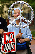 Sally Streeter carries a large tinfoil peace sign as members of the Portland Peaceful Response Coalition gather for their weekly war protest about the downtown area.