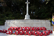 Wreaths of poppies laid at the Cross of Sacrifice during the Remembrance Sunday ceremony at the Hodogaya, Commonwealth War Graves Cemetery in Hodogaya, Yokohama, Kanagawa, Japan. Sunday November 11th 2018. The Hodagaya Cemetery holds the remains of more than 1500 servicemen and women, from the Commonwealth but also from Holland and the United States, who died as prisoners of war or during the Allied occupation of Japan. Each year officials from the British and Commonwealth embassies, the British Legion and the British Chamber of Commerce honour the dead at a ceremony in this beautiful cemetery. The year 2018 marks the centenary of the end of the First World War in 1918.