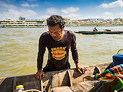 14 OCTOBER 2015 - BANGKOK, THAILAND: A diver climbs back into his dive boat after surfacing in the Chao Phraya River in Bangkok. Divers work in two man teams on small boats in the Chao Phraya River. One person stays in the boat while the diver scours the river bottom for anything that can be salvaged and resold. The divers usually work close to shore because the center of the river is a busy commercial waterway with passenger boats and commercial freight barges passing up and down the river all day long. The Chao Phraya is a dangerous river to dive in. It's deep, has large tidal fluctuations, is fast flowing and badly polluted. The divers make money only when they sell something.    PHOTO BY JACK KURTZ
