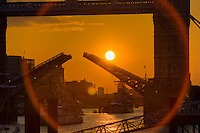 sun sets behind an open tower bridge bascules
